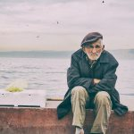 older man sitting on a dock
